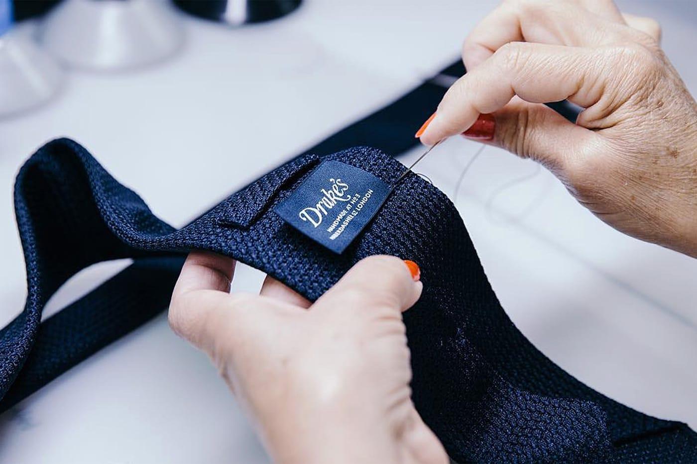 自社工場において職人によりハンドメイドで仕立てられる英国製ネクタイ